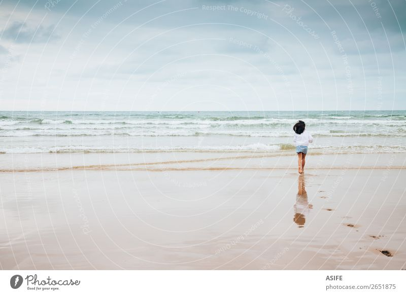 Girl enjoying the beach with bad weather Joy Beach Ocean Waves Sports Child Infancy Nature Landscape Sand Sky Clouds Bad weather Footprint To enjoy Jump Wet