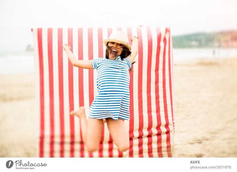 Crazy for vacation Joy Happy Beautiful Playing Vacation & Travel Summer Beach Child Dress Hat Brunette Smiling Laughter Jump Funny Cute Blue Red kid girl