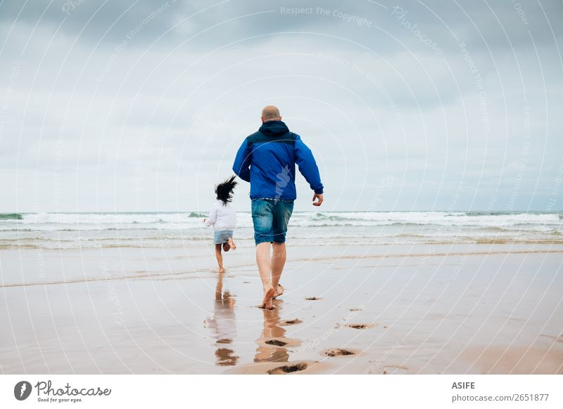 Father and daughter playing on the beach in a cloudy day Joy Happy Leisure and hobbies Playing Beach Ocean Child Parents Adults Family & Relations Clouds