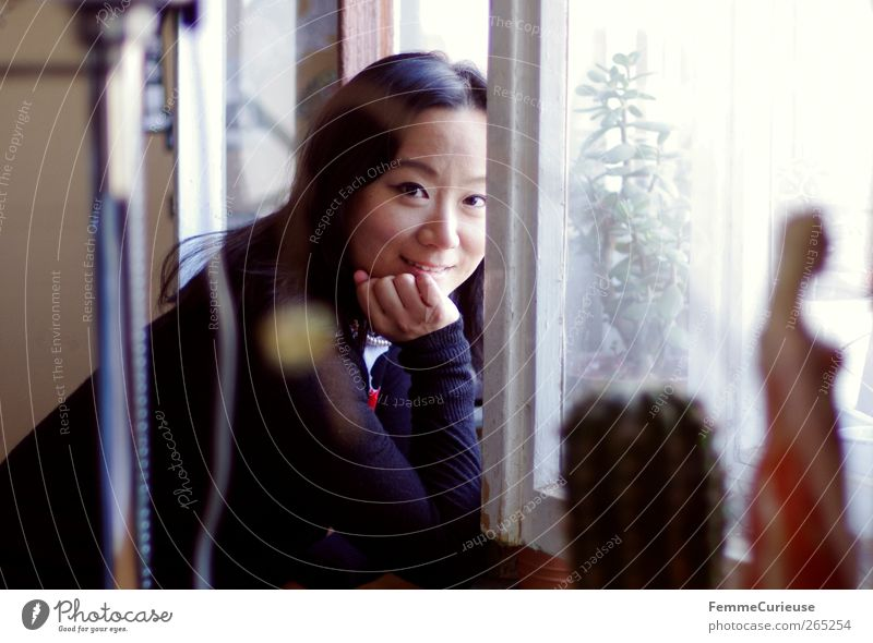 At the window. Young woman Youth (Young adults) Woman Adults Head Hand 18 - 30 years Esthetic Contentment Relaxation Leisure and hobbies Identity Uniqueness
