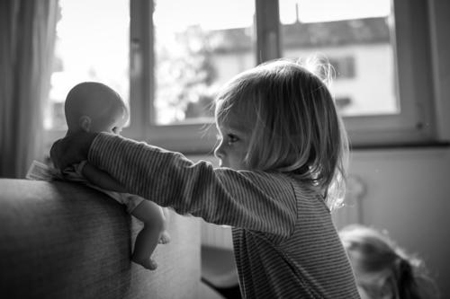 Girl with doll Feminine Infancy 1 Human being 1 - 3 years Toddler Playing Authentic Beautiful Gray Black White Happiness Contentment Joy Identity Independence