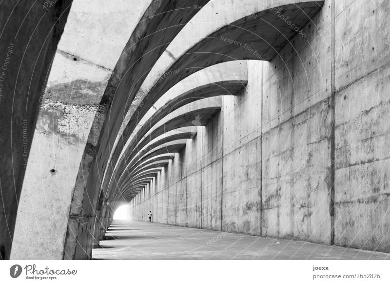Fair-faced concrete protective wall with curved supporting arches, in which a jogger Wall (building) Contrast Day Exterior shot Subdued colour Man White Black