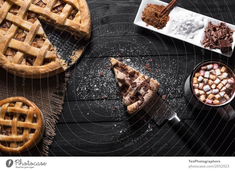 Apple pies with slice and hot chocolate. Cake Dessert Candy Hot Chocolate Plate Cup Knives Table Kitchen Black Tradition Thanksgiving day above view American