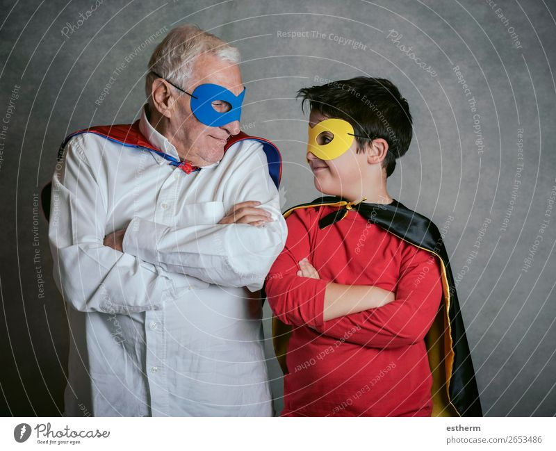 Grandfather With Grandson dressed as a superhero on gray background Lifestyle Joy Adventure Feasts & Celebrations Carnival Fairs & Carnivals Retirement