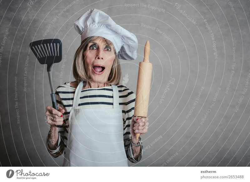 surprised senior woman with cook hat and rolling pin and spatula Nutrition Diet Lifestyle Leisure and hobbies Kitchen Restaurant Retirement Feminine