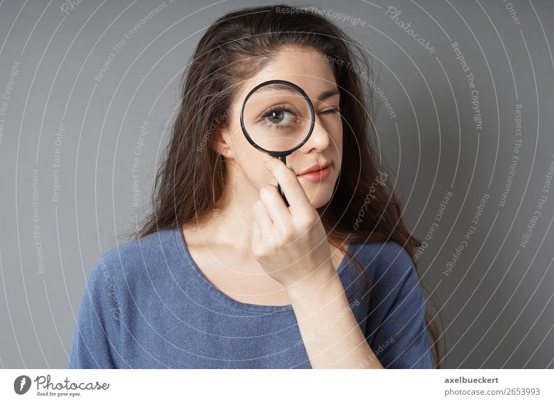 young woman looks through magnifying glass Lifestyle Business Human being Feminine Young woman Youth (Young adults) Woman Adults 1 18 - 30 years Brunette