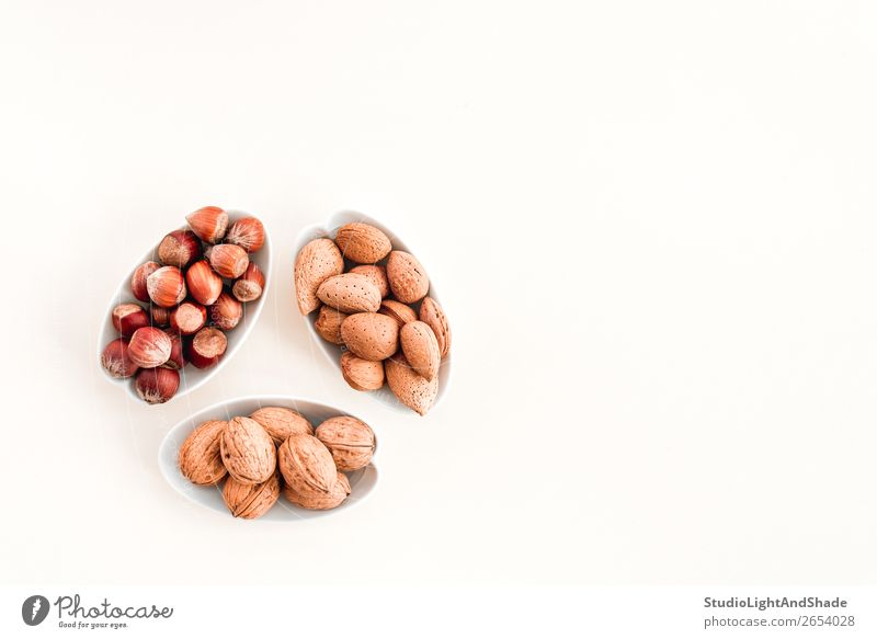 Plates with almonds, hazelnuts and walnuts Colour White Eating Natural Copy Space Brown Nutrition Fresh Cooking Vegetarian diet Diet Bowl