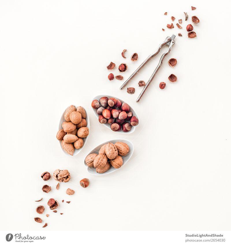 Variety of nuts and nutcracker Nutrition Eating Vegetarian diet Diet Plate Fresh Natural Brown White Colour Decline hazelnut hazelnuts Almond almonds walnut
