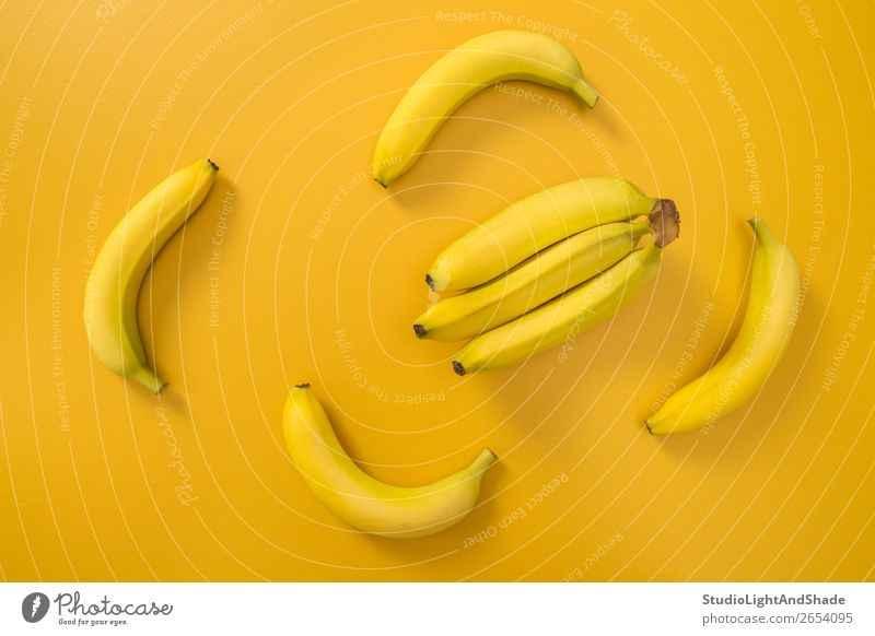 Bananas on bright yellow background Fruit Nutrition Vegetarian diet Diet Design Exotic Joy Happy Healthy Eating Summer Nature Simple Fresh Bright Modern Natural