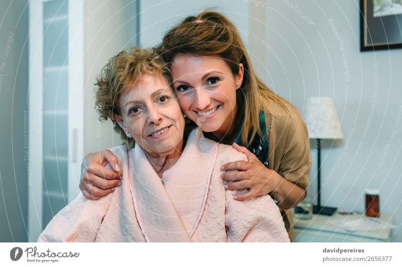 Female caretaker posing with elderly patient Happy Health care Illness Lamp Bedroom Doctor Hospital Human being Woman Adults Old Smiling Sit Embrace Authentic