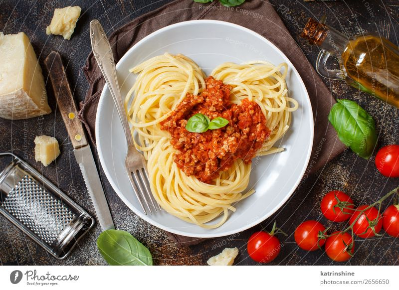 Spaghetti pasta with bolognese sauce Meat Cheese Herbs and spices Lunch Dinner Plate Fork Wood Bright Above Tradition Basil Beef Bolognese Cooking Dish food