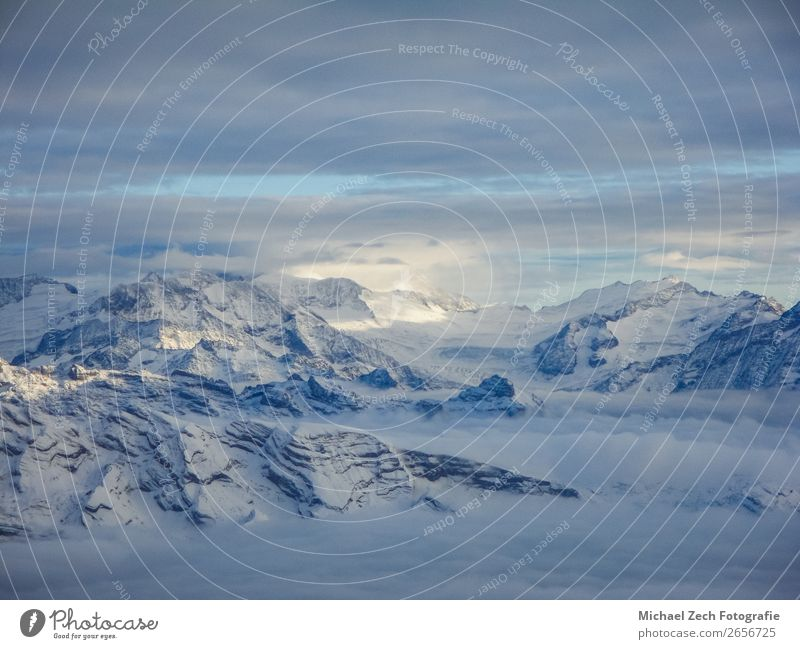 Amazing aerial view of misty swiss alps and clouds Vacation & Travel Winter Snow Mountain Nature Landscape Sky Clouds Horizon Weather Fog Rock Alps Peak