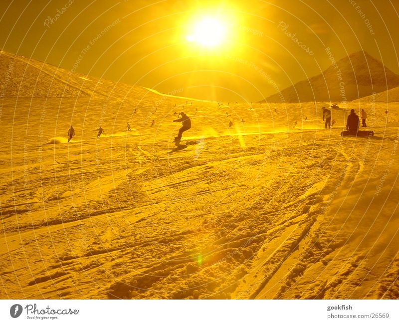 fast snowing Snowboard Yellow Action Sports Sun Yellowness Back-light Sunbeam Ski run Ski resort Snowboarder Snowboarding Swing Downward Many Skier Snow track