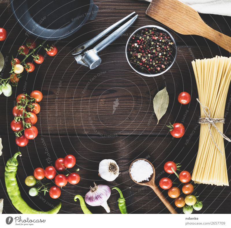 pasta raw tied up with rope Vegetable Dough Baked goods Herbs and spices Pan Spoon Table Kitchen Wood Line Fresh Large Long Above Brown Yellow Red Black Colour