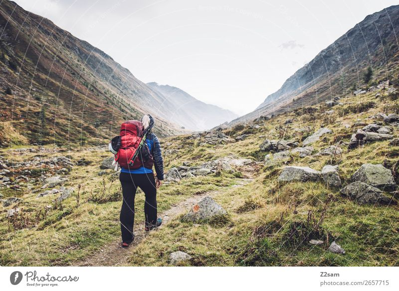 Young woman climbing the Timmelsjoch | E5 Vacation & Travel Adventure Expedition Mountain Hiking Nature Landscape Autumn Fog Meadow Rock Alps Jacket Backpack