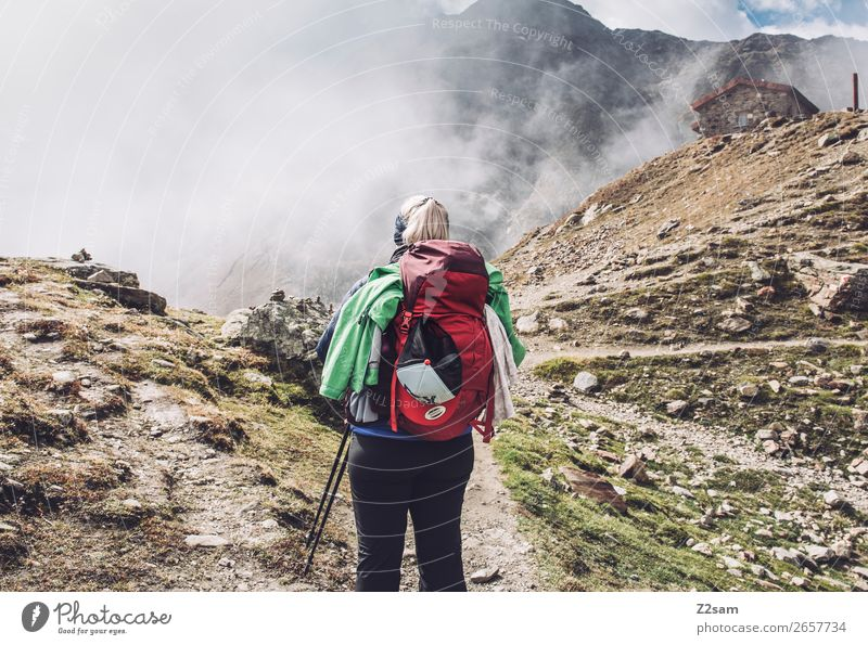 Young woman hiking, Timmelsjoch E5. Vacation & Travel Expedition Hiking Youth (Young adults) Nature Landscape Sky Clouds Autumn Beautiful weather Fog Alps