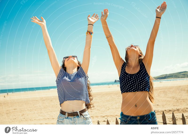 Girls greeting the sun Joy Happy Tourism Summer Beach Ocean Woman Adults Friendship Youth (Young adults) Arm Nature Sand Sky Bikini Sunglasses Smiling Laughter