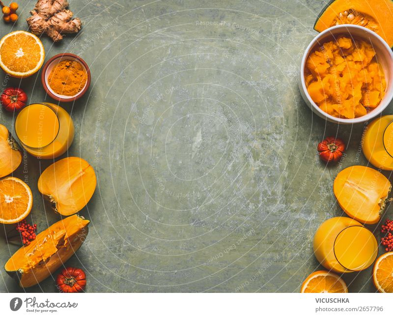 Orange color smoothie ingredients background for cold season with  pumpkin, orange fruits, ginger, turmeric and persimmon fruits , top view, frame, copy space. Healthy mood and energy smoothie drinks