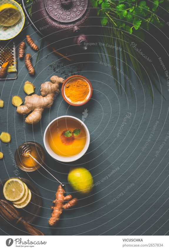 Healthy turmeric spice tea preparation on gray background with teapot, cup of tea,  lemon,  ginger, cinnamon sticks and honey , top view.  Immune boosting remedy , detox and dieting concept