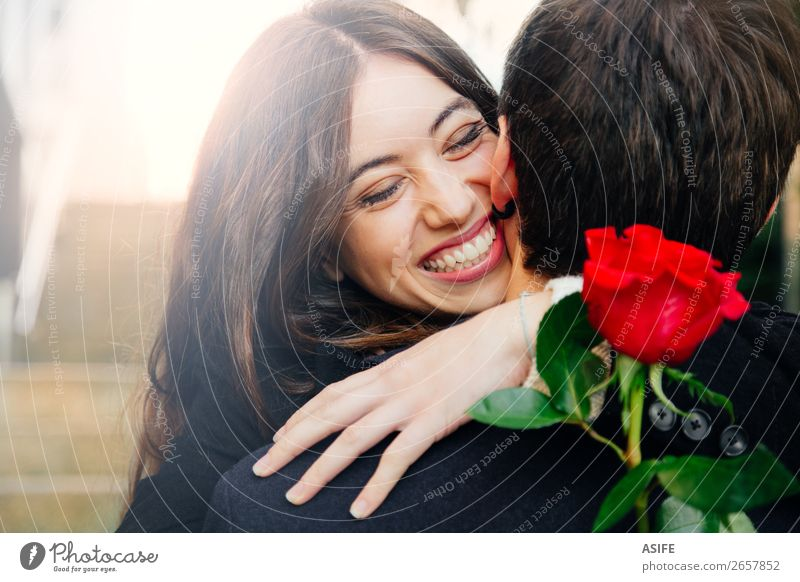 Happy couple in love with a rose Joy Beautiful Winter Feasts & Celebrations Valentine's Day Woman Adults Man Couple Hand Autumn Flower Coat Kissing Smiling