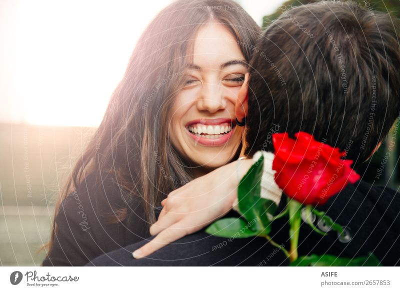Happy couple hugging each other Woman Man Beautiful Red Hand Flower Joy Winter Black Adults Autumn Love Emotions Laughter Feasts & Celebrations