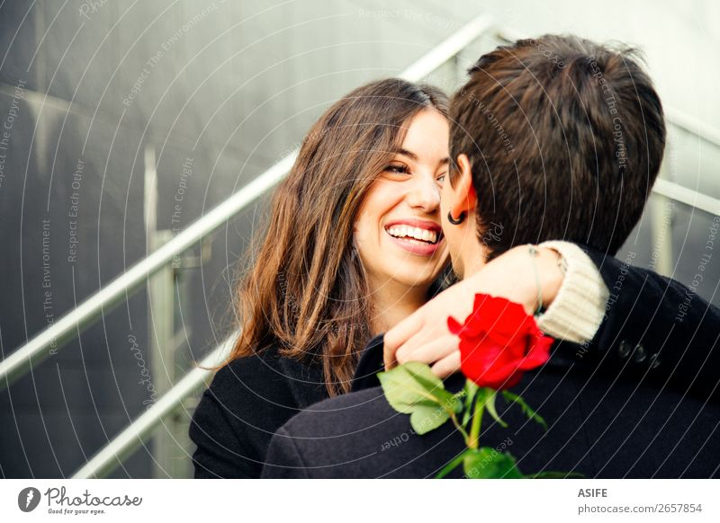 Happy couple in love with a rose on the street Woman Man Beautiful Red Hand Flower Joy Winter Black Adults Autumn Love Feasts & Celebrations Couple Together