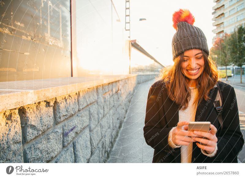 Happy young woman with her mobile on the street Woman Youth (Young adults) Beautiful Hand Sun Joy Winter Street Lifestyle Adults Autumn Laughter Technology