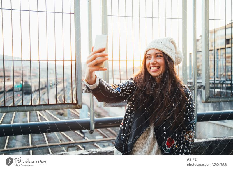 Selfie girl in the city at sunset Happy Beautiful Winter PDA Technology Woman Adults Youth (Young adults) Autumn Train station Street Railroad tracks Fashion