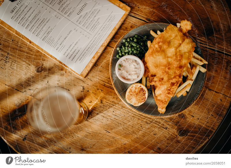 Fish and chips Food Seafood Lunch Beer Table Restaurant Eating Wood Gold Tradition Sauce British Potatoes Meal Peas Frying Dish Tartar Menu Pub Tavern Lemon
