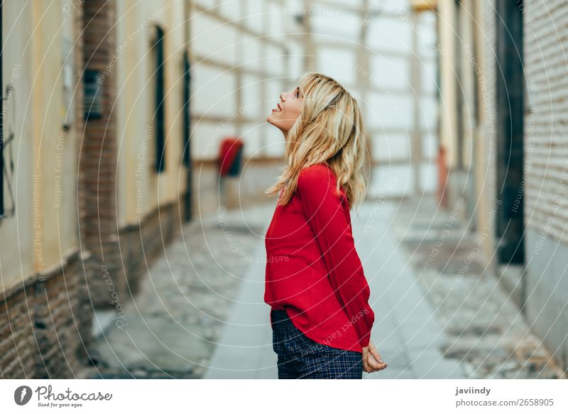 Happy young blond woman walking down the street. Woman Human being Youth (Young adults) Young woman Beautiful White Red 18 - 30 years Street Lifestyle Adults