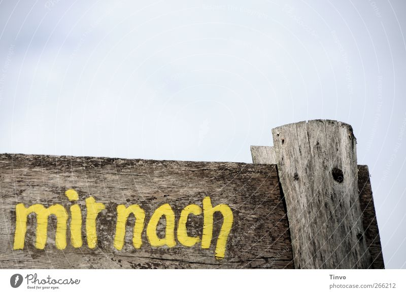 "Wooden sign with inscription ""mir nach"" (after me) Sky Characters Signage Warning sign Old Blue Brown Yellow Gray Weathered Signs and labeling Word Colour photo"