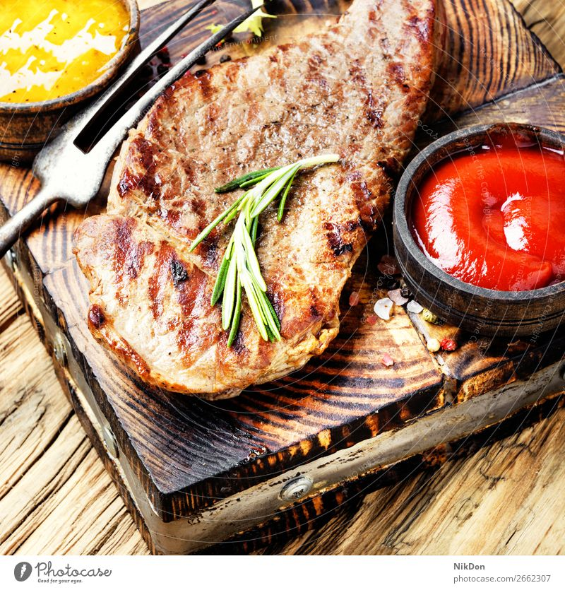 Beef steak with twig rosemary beef meat food grilled barbecue roasted beefsteak sauce ketchup sirloin wooden fillet bbq tenderloin fork table eating restaurant