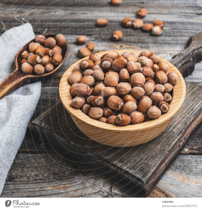 hazelnut nuts in a brown wooden bowl Fruit Nutrition Vegetarian diet Bowl Table Wood Old Eating Fresh Natural Brown dry Edible filbert food Heap husk