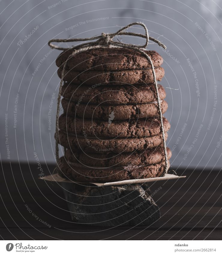 stack of round chocolate cookies tied with a rope Cake Dessert Candy Nutrition Table Rope Group Eating Dark Delicious Brown background Baking biscuit food