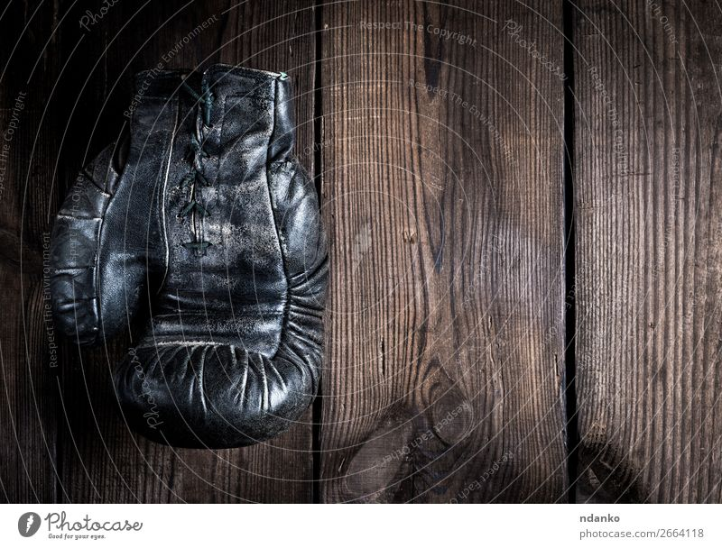 very old leather black boxing glove with laces Lifestyle Fitness Sports Leather Gloves Wood Old Dark Retro Brown Black Protection Aggression Competition one