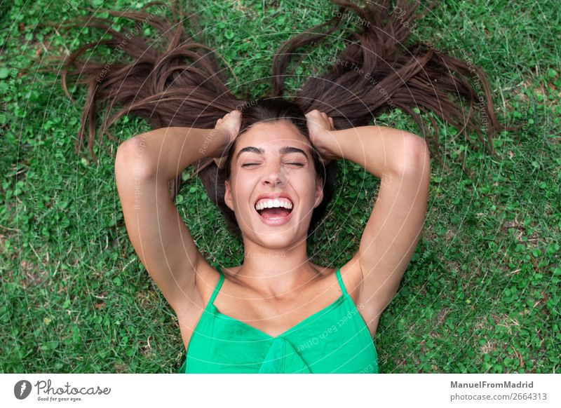 young cheerful woman lying down on the grass Lifestyle Happy Beautiful Leisure and hobbies Summer Human being Woman Adults Nature Grass Park Meadow Smiling