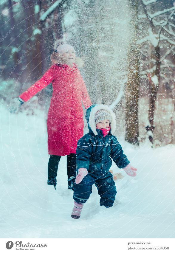 Mother is playing with her little daughter outdoors in winter Lifestyle Joy Happy Winter Snow Winter vacation Human being Child Toddler Girl Young woman