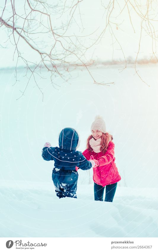 Teenage girl enjoying snow with her little sister Lifestyle Joy Happy Winter Snow Winter vacation Human being Child Toddler Girl Woman Adults Mother