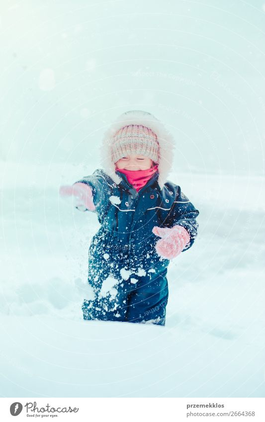 Happy little girl enjoying snow. Child playing outdoors walking through deep snow in wintertime while snow falling. Toddler is wearing dark blue snowsuit