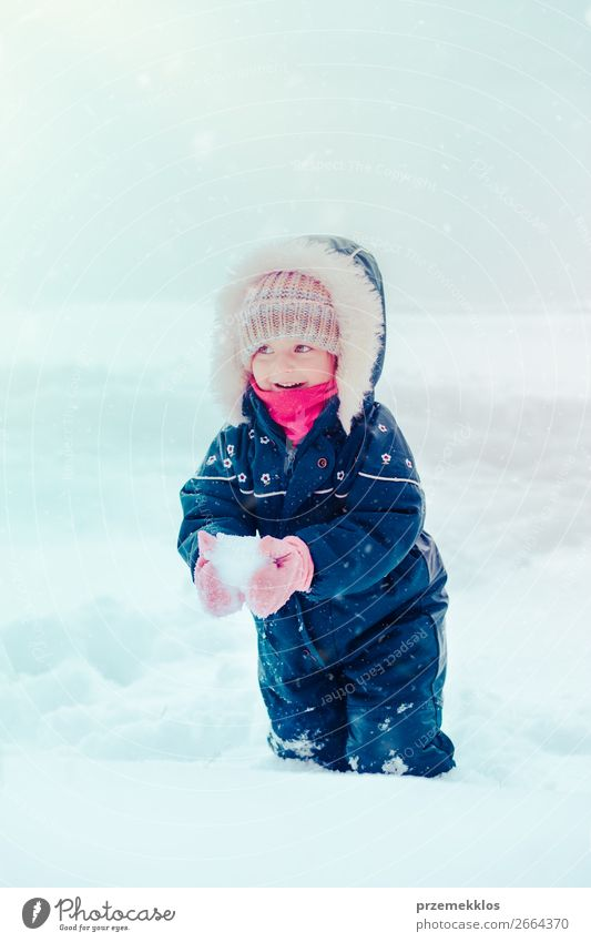 Happy little girl enjoying snow in wintertime while snow falling Lifestyle Joy Winter Snow Winter vacation Child Girl Infancy 1 Human being 3 - 8 years Snowfall