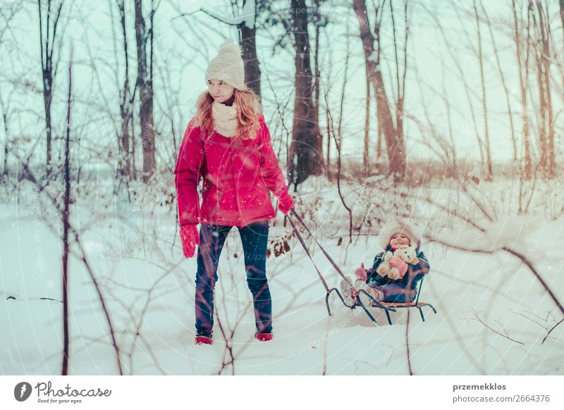 Teenage girl pulling sled with her little sister through forest Lifestyle Joy Happy Winter Snow Winter vacation Human being Child Baby Toddler Girl Young woman