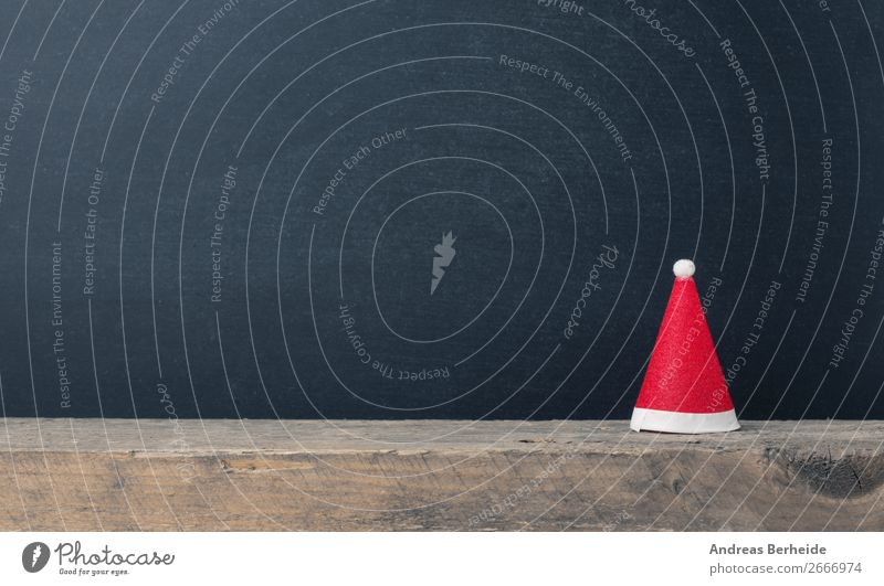 Santa Claus cap on a wooden board in front of a blackboard Winter Christmas & Advent Blackboard Hat Cap Decoration Tradition decor Symbols and metaphors concept