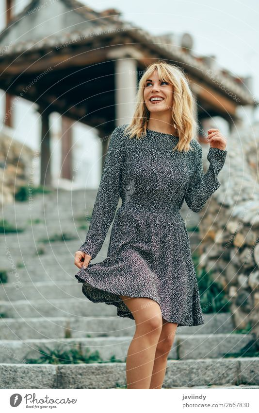 Smiling blonde girl wearing dress dancing outdoors. Woman Human being Youth (Young adults) Beautiful White Joy 18 - 30 years Street Lifestyle Adults Autumn