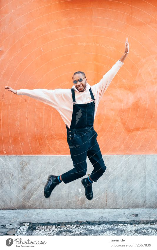 Young black man wearing casual clothes jumping outdoors Lifestyle Joy Happy Beautiful Human being Masculine Young man Youth (Young adults) Man Adults 1