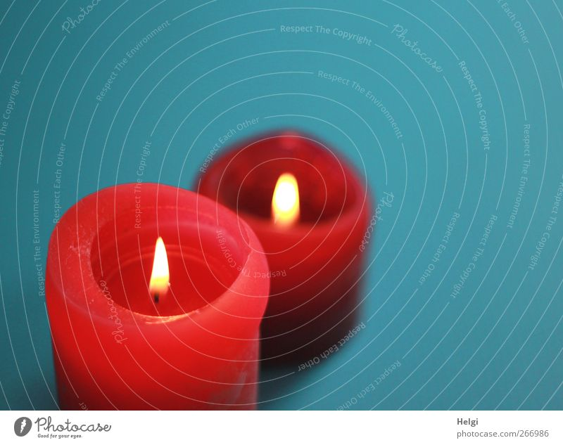 two red burning candles stand one behind the other in front of a turquoise background Decoration shoulder stand Flame Wick Wax Illuminate Stand