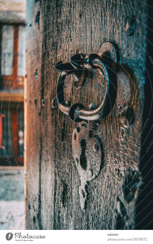 A lock and a handle of a medieval wooden door captured from the side with the village's street in the background Design Vacation & Travel Tourism