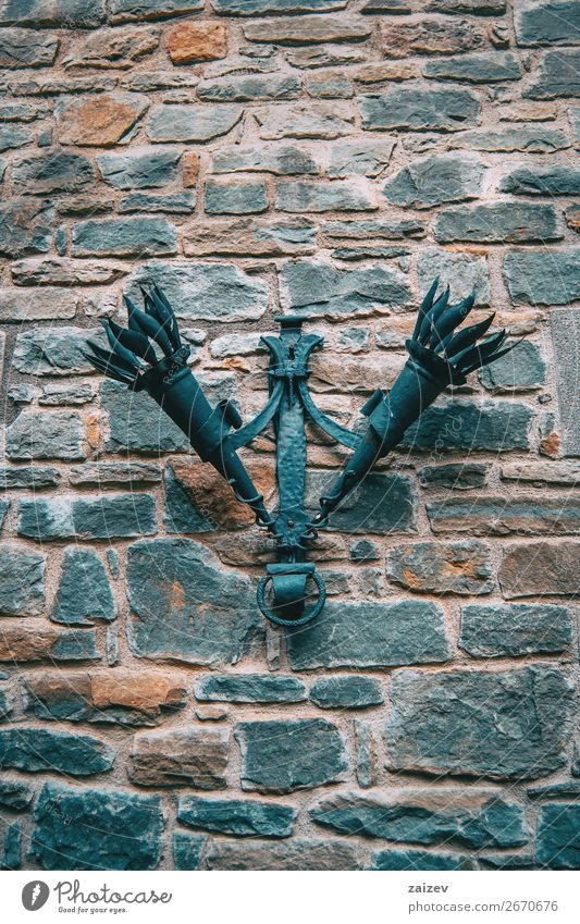 Two ancient torches hanging from a stone wall in a medieval village Design Vacation & Travel Tourism Decoration Culture Village Town Building Street Stone Metal