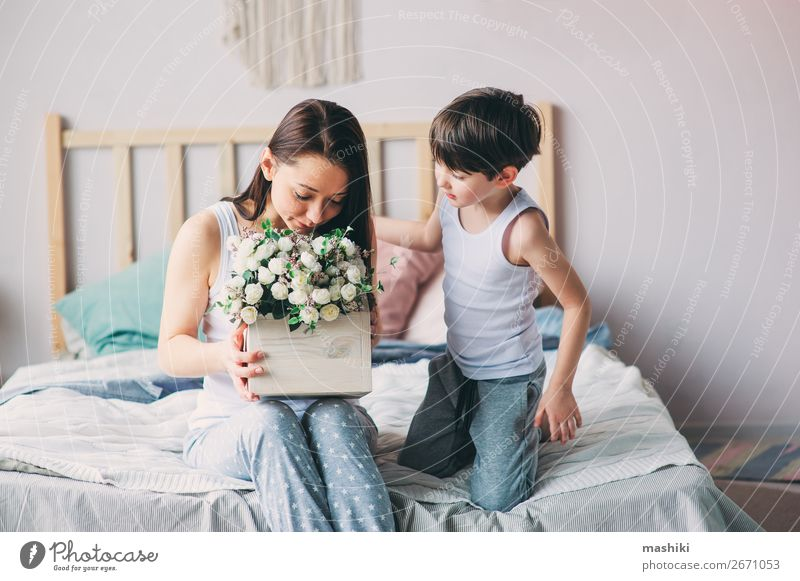 happy child boy giving flowers to mom Lifestyle Joy Bedroom Mother's Day Child Toddler Boy (child) Parents Adults Family & Relations Infancy Flower Smiling Love
