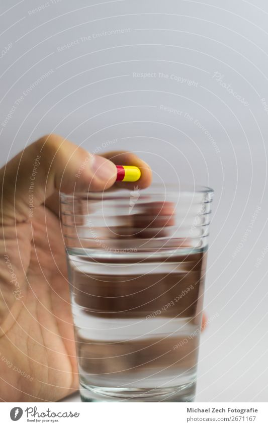 men gives a red and yellow colored pill in a glass of water Bowl Medical treatment Illness Medication Science & Research Hand Wood Blue Yellow Pink White Colour