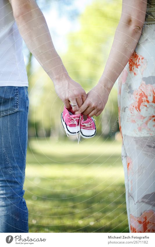 Parents walk together in park, holding baby shoes in hands Happy Beautiful Garden Baby Boy (child) Woman Adults Man Mother Father Family & Relations Couple Hand